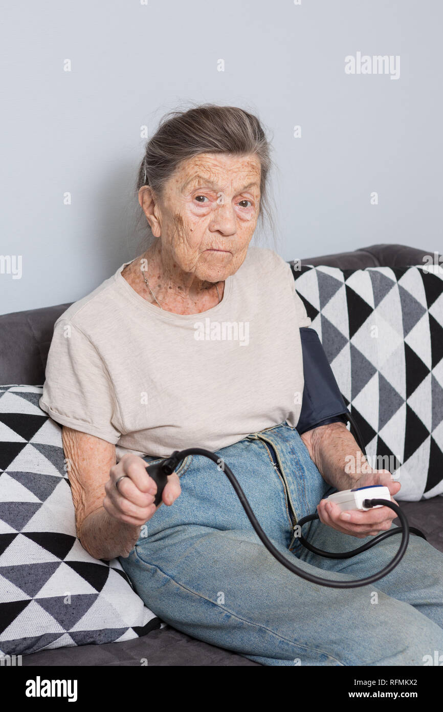 The topic is very old person and health problems. A senior Caucasian woman, 90 years old, with wrinkles and gray hair, sits home on sofa and uses a bl - Stock Image