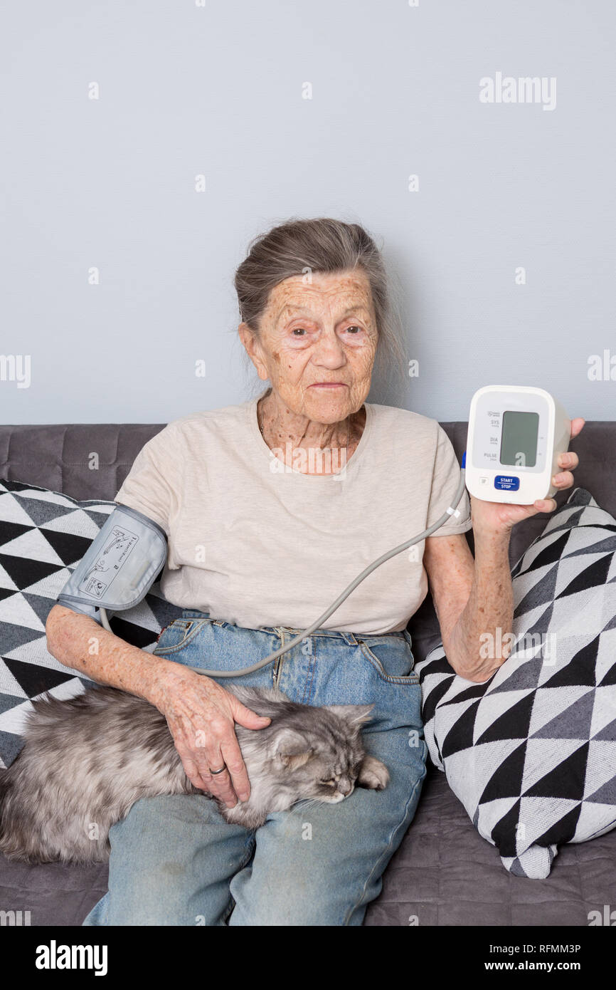 The topic very old person and monitor health. senior Caucasian woman, 90 years old, with wrinkles and gray hair, sits home on a sofa with a pet cat an - Stock Image