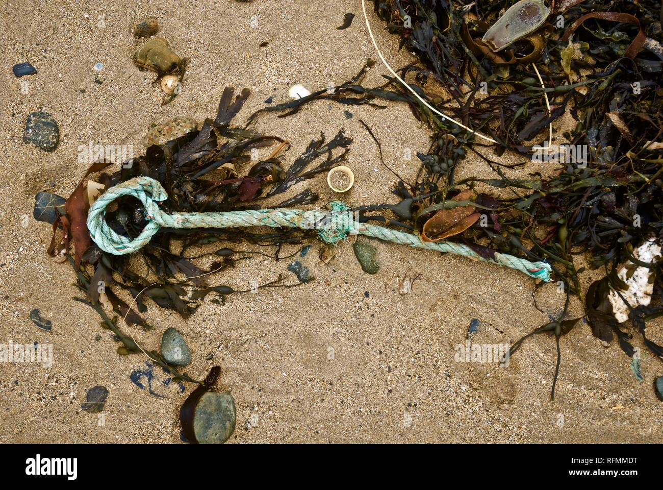 Plastic rope waste and pollution washed up on a beach in Rhosneigr, Anglesey, North Wales, UK - Stock Image
