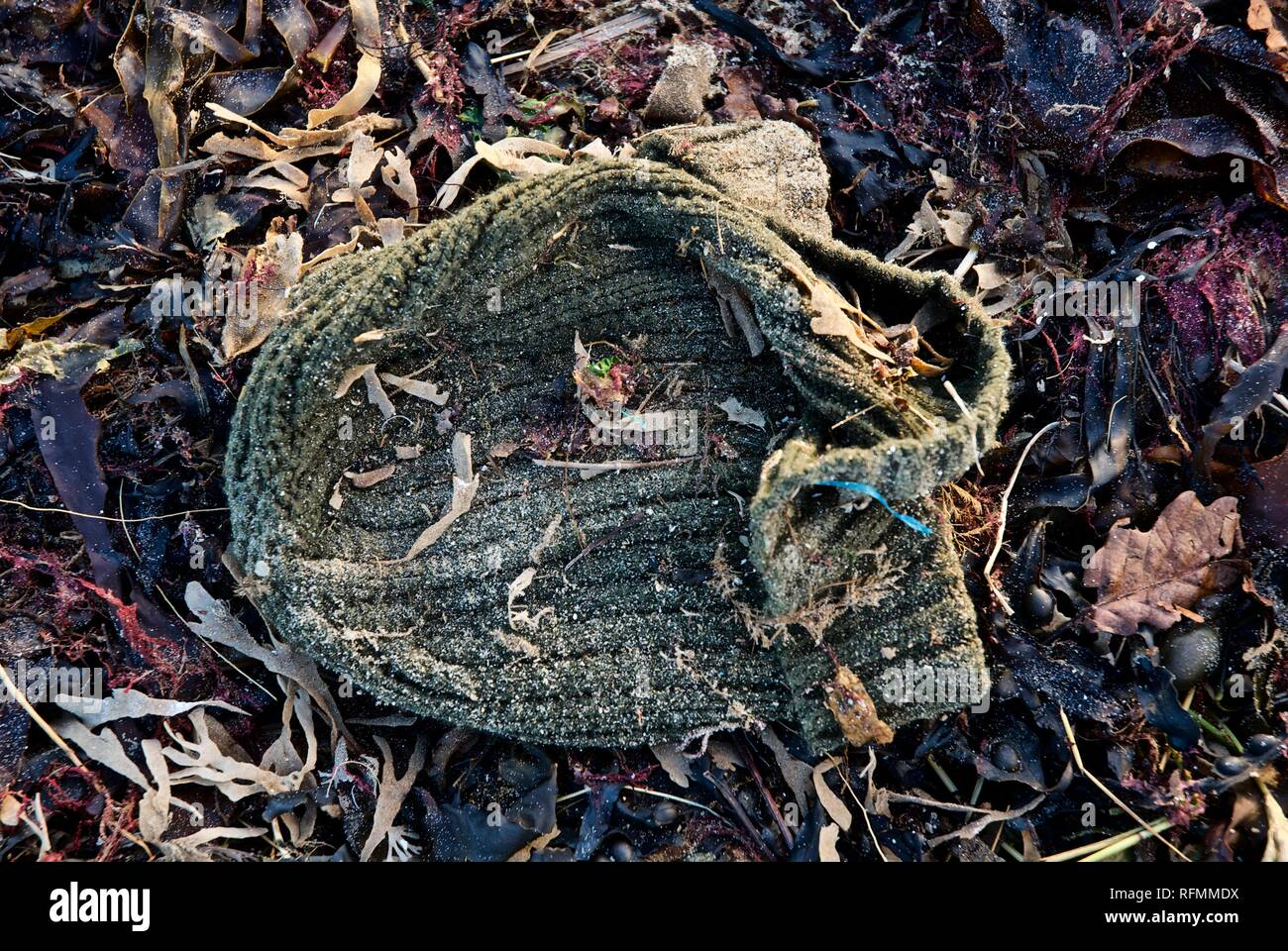 A discarded hat, sea waste washed up on a beach in Rhosneigr, Anglesey, North Wales, UK - Stock Image