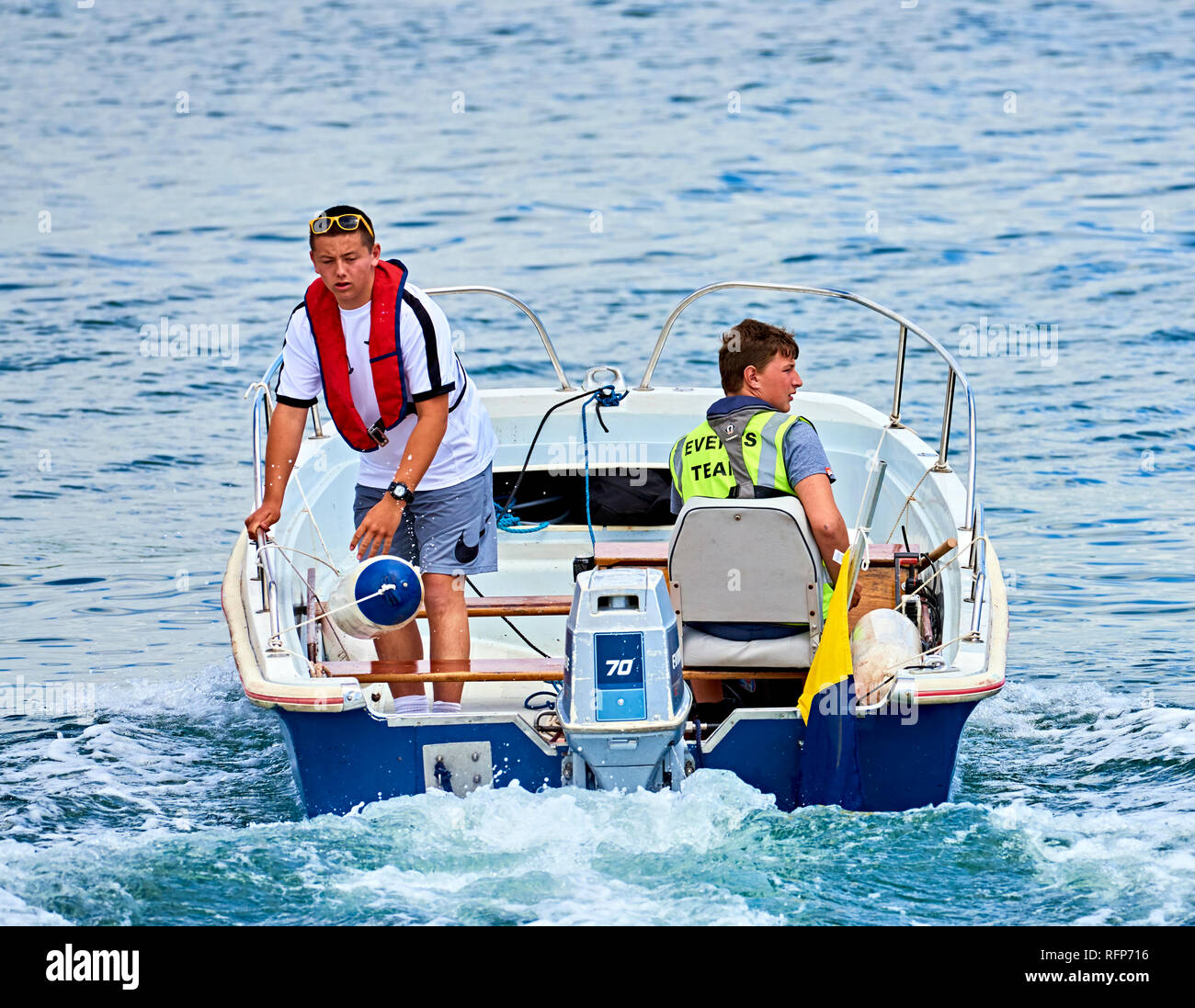 Two young men operate a small safety boat at a waterborne event. - Stock Image