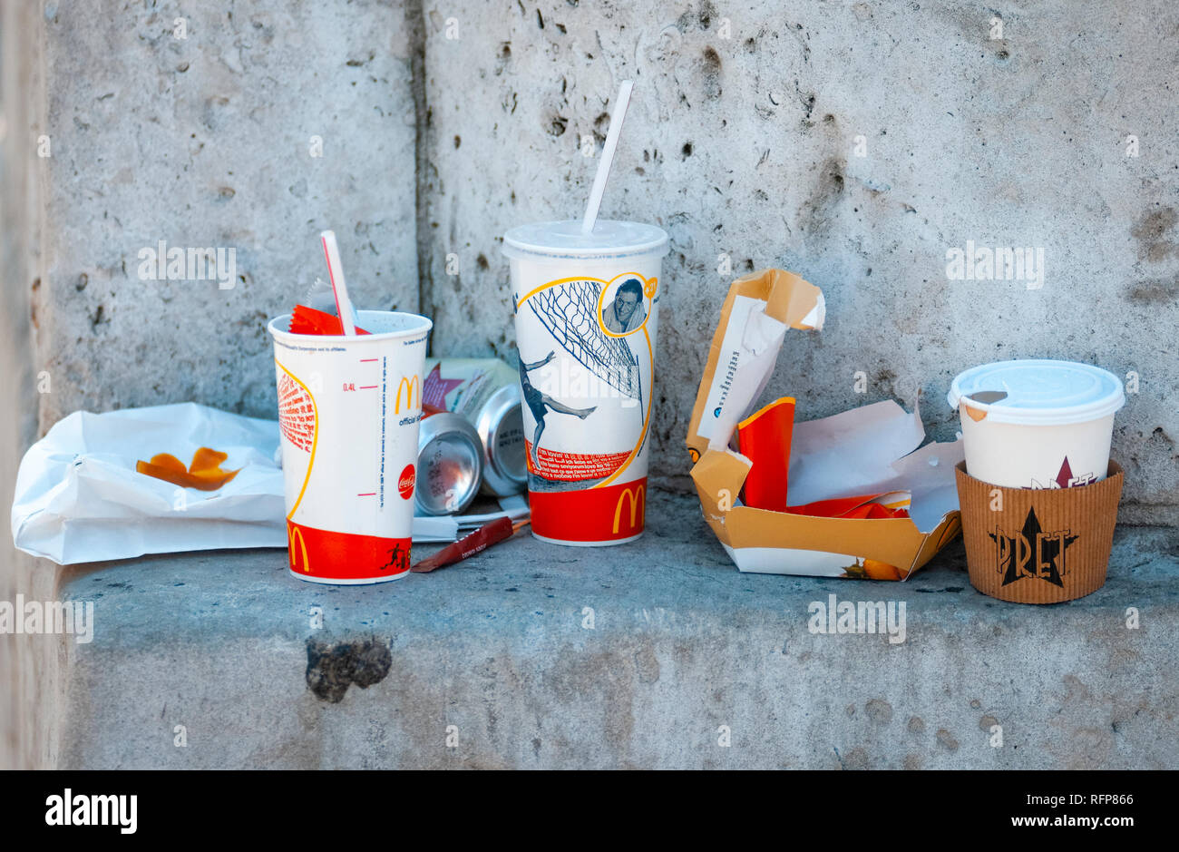 McDonald's take away wrappers left on a wall in the street, Mcdonald's is the worlds biggest chain of fast food restaurants Stock Photo