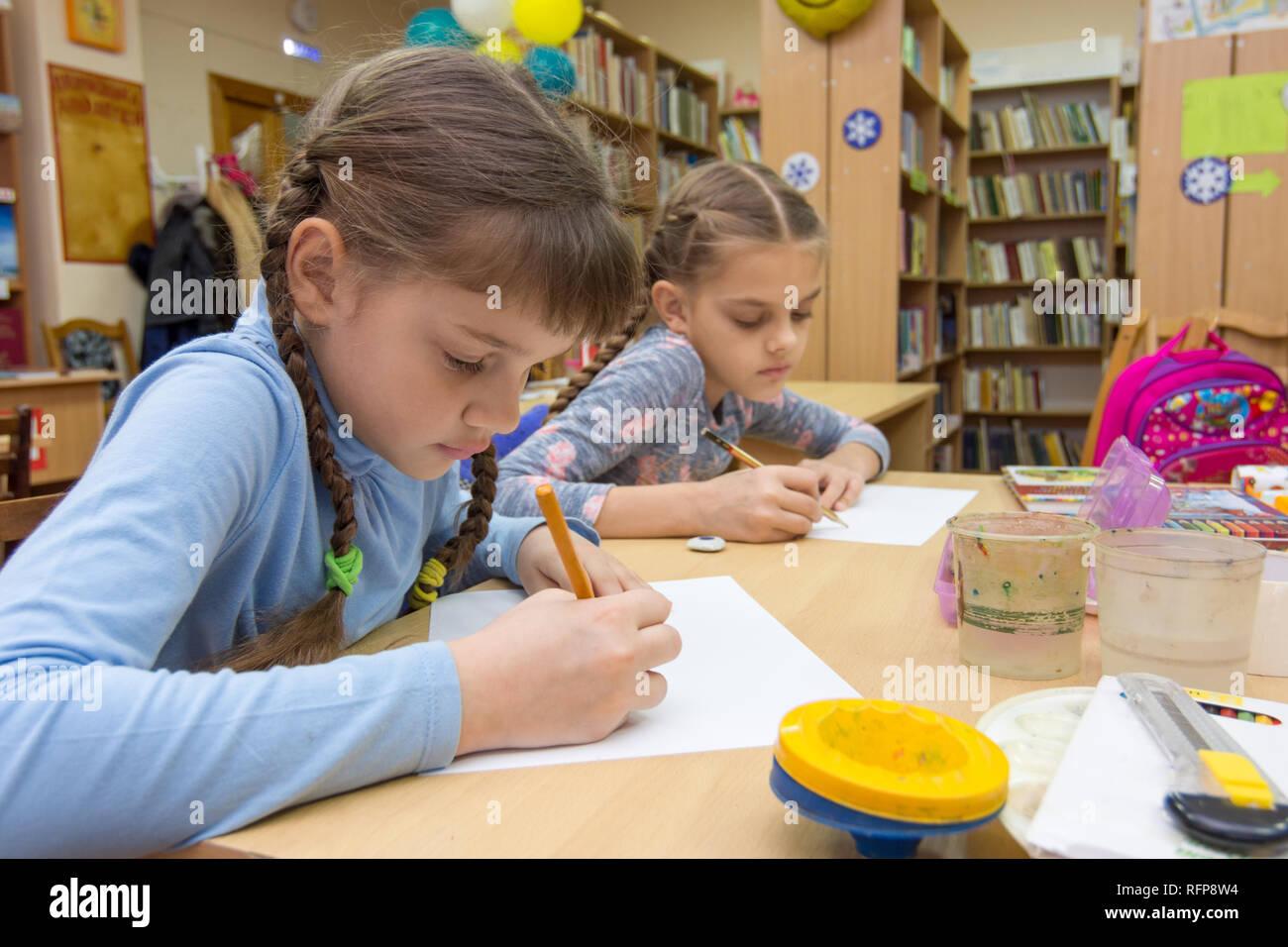 Schoolgirls in extracurricular activities draw in the library - Stock Image