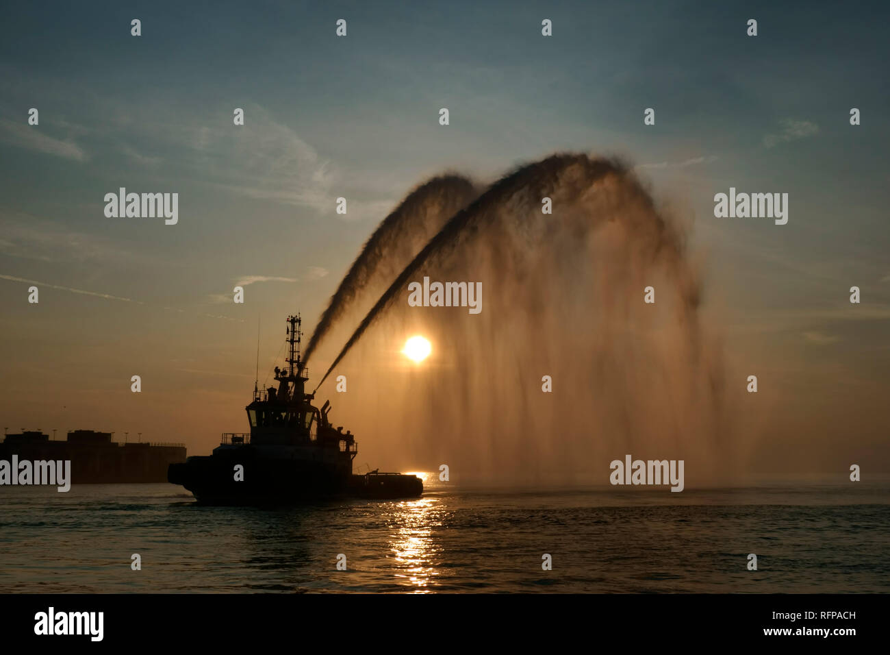 Fire boat in the harbor. Water cannon salute during an event. - Stock Image
