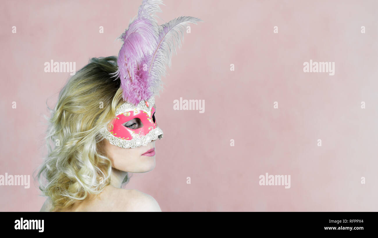 Mysterious woman seduces eyes. A girl with white hair in a mask on her face with feathers of birds on a pink background. - Stock Image