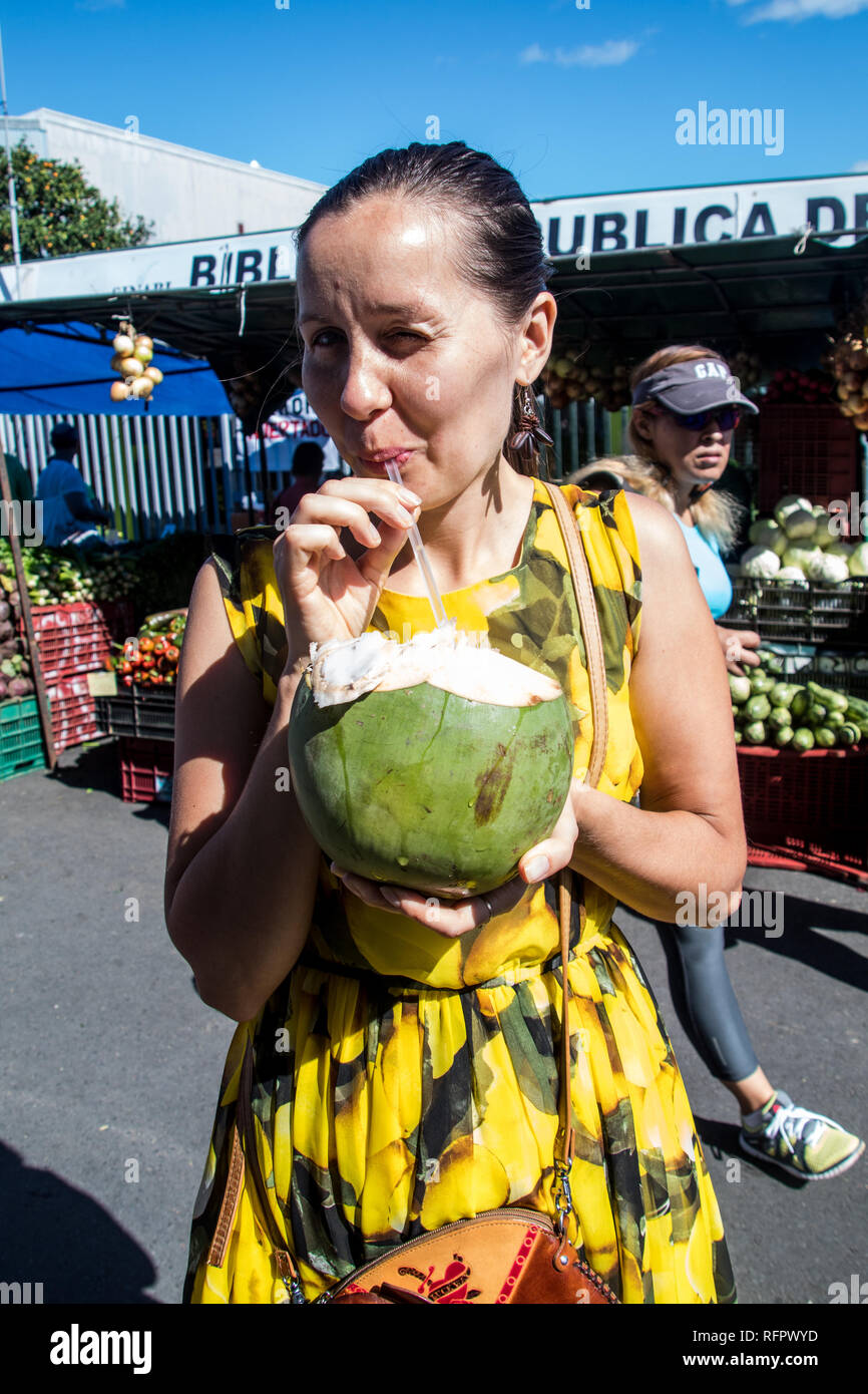 A portrait of a woman in a yellow dress drinking cocos juice directly out of a coconut at sunday's farmers market in Santa Ana, Costa Rica. - Stock Image