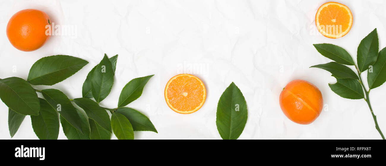 many fresh oranges and green leaves on white crumpled paper background - Stock Image