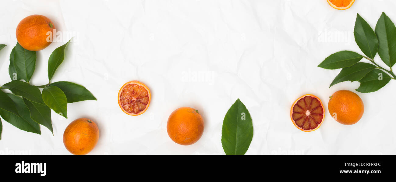 many fresh blood oranges and green leaves on white crumpled paper background - Stock Image