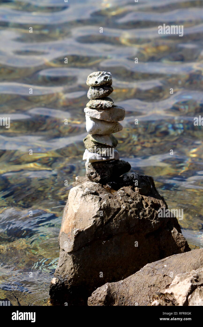 Beach stones stacked on one straight pile on top of large rock used for meditation or as artistic installation with clear sea in background on warm - Stock Image