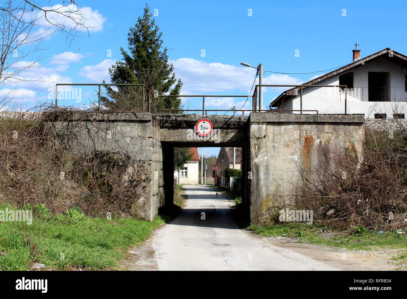 Old train overpass with cracked concrete partially overgrown with dried plants without leaves with narrow paved road going through it and houses - Stock Image