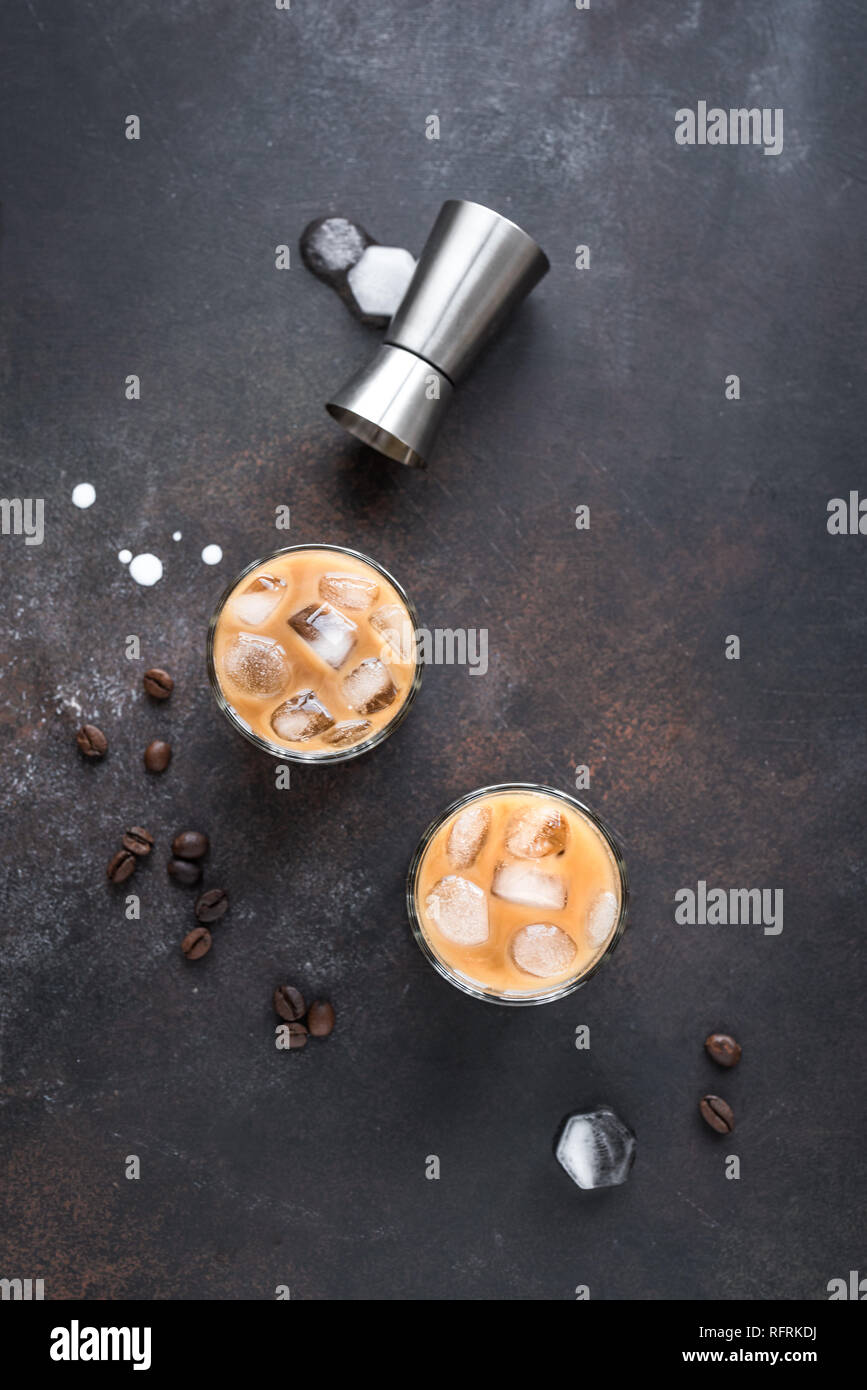 White Russian Cocktails with Vodka, Coffee Liquor and Cream. Homemade iced Alcohol Boozy White Russian or Lebowski drink with coffee beans on rustic b Stock Photo