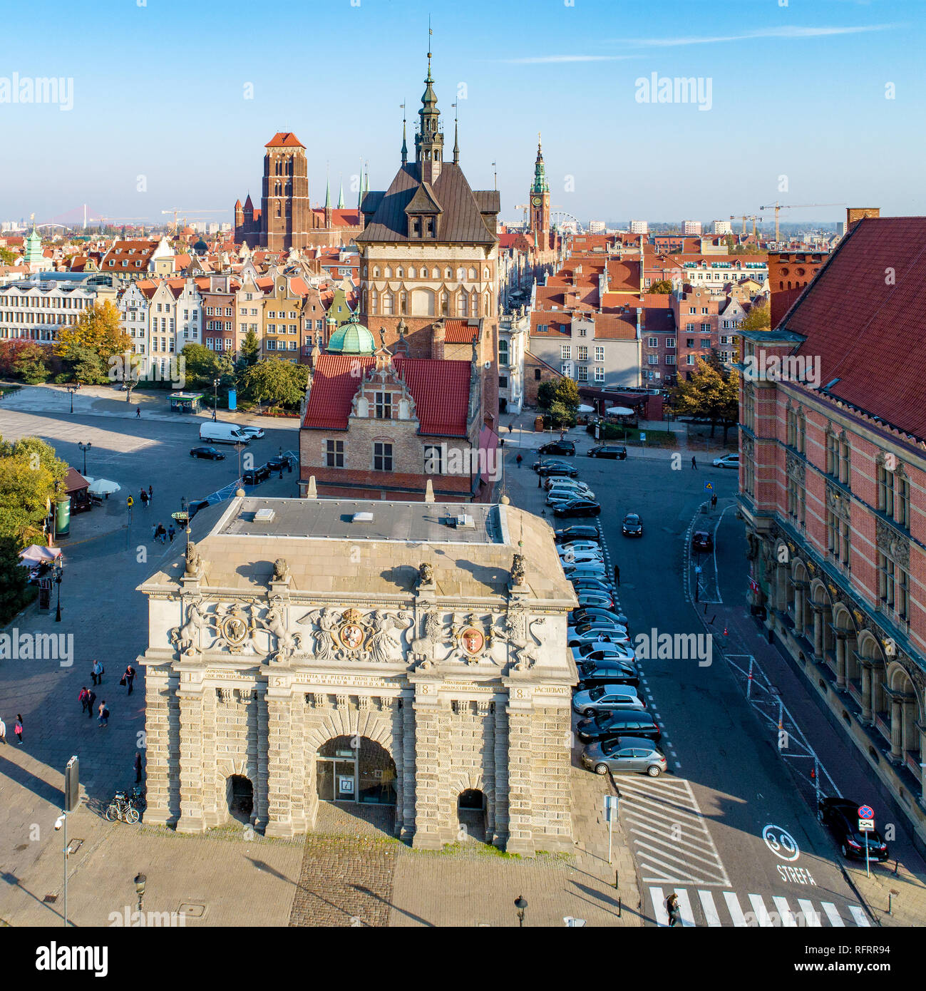 Gdansk, Poland. Old city with Renaissance Gate, called Brama Wyzynna ,  (Upland or High Gate) Prison Gate with torture chamber, St Mary church tower - Stock Image