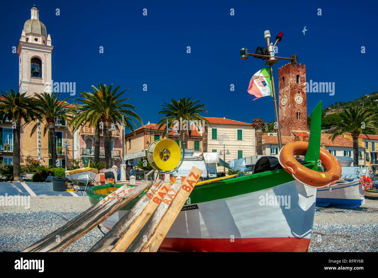 Old colorful wooden fishing boats on the beach, Noli, Italy with historic medieval waterfront buildings behind and tropical palm trees on the promenad - Stock Image