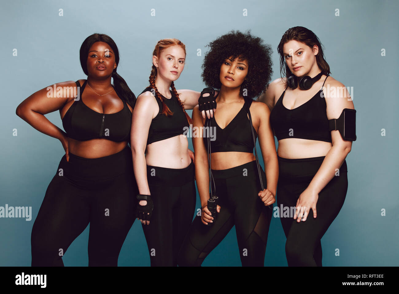 Group of women of different race and body size dressed in sportswear standing together against grey background. Diverse women in sports clothing looki - Stock Image