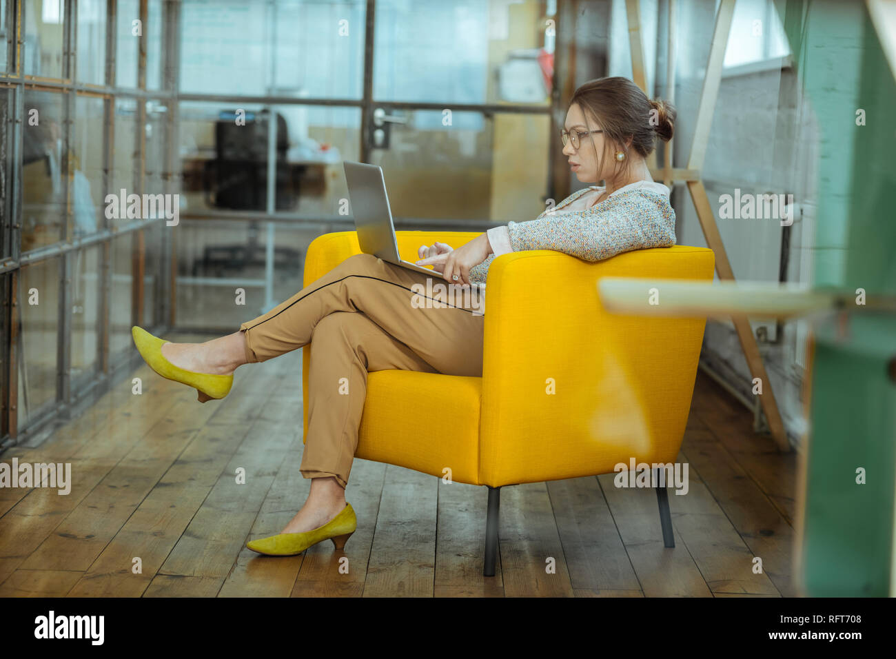 Dark-haired businesswoman sitting in nice comfy yellow armchair - Stock Image