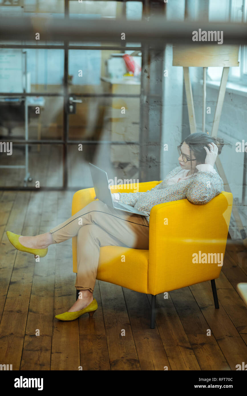 Businesswoman sitting in comfy armchair while working on laptop - Stock Image