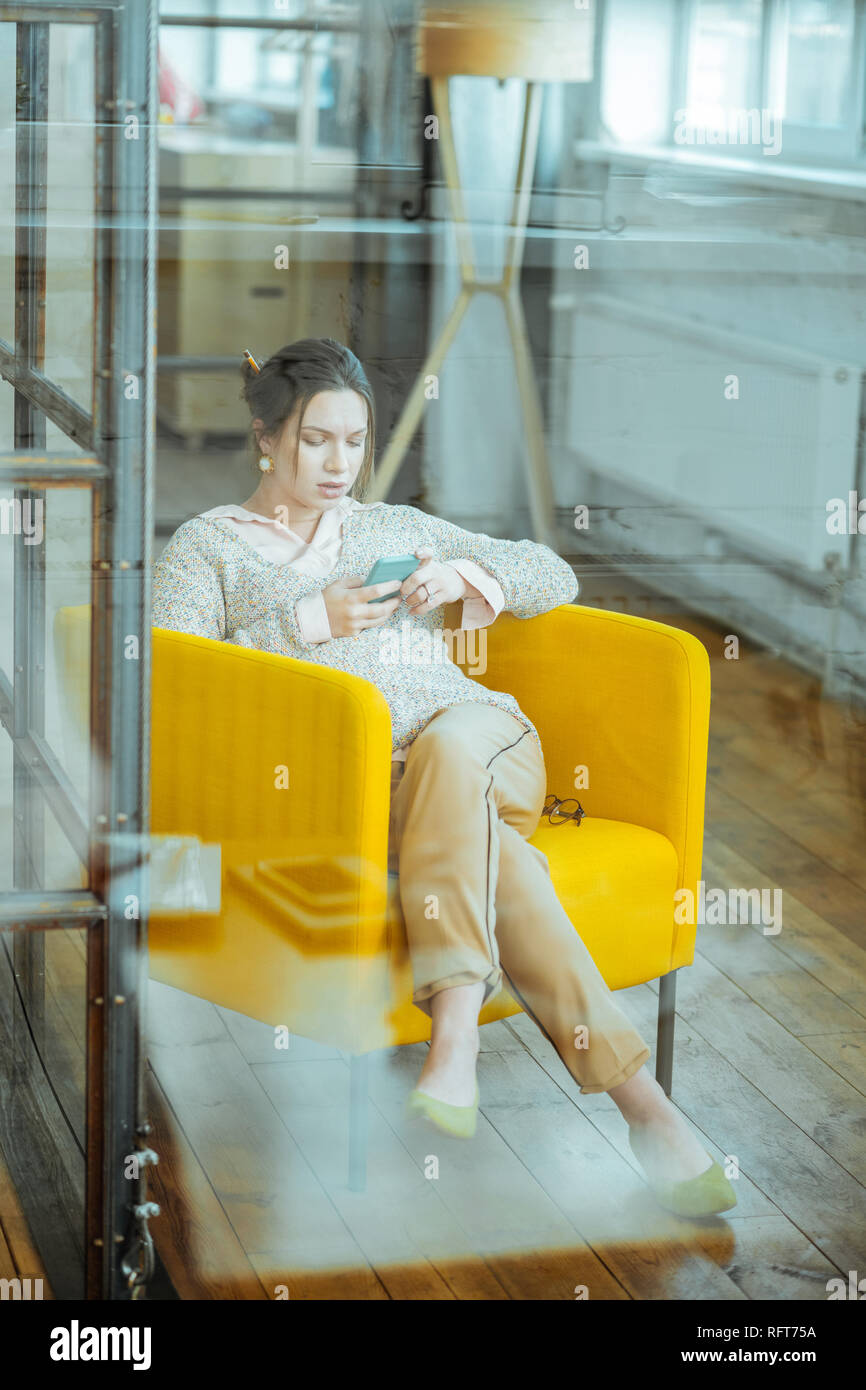 Pregnant businesswoman chilling while sitting in comfy armchair - Stock Image