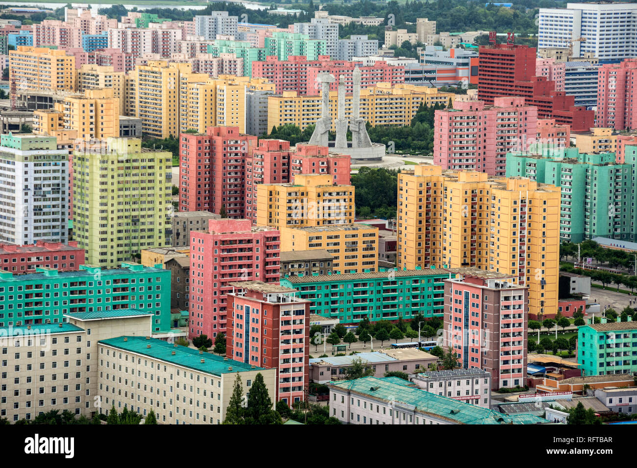 Workers' Party Monument amid painted blocks of flats, seen from Juche Tower, Pyongyang, North Korea, Asia - Stock Image