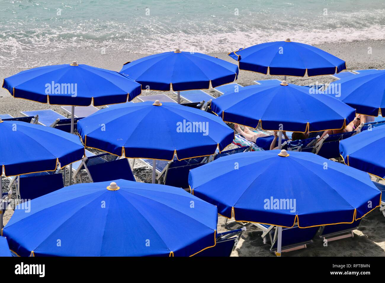 Blue beach umbrellas on an Italian beach overlooking the Mediterranean - Stock Image
