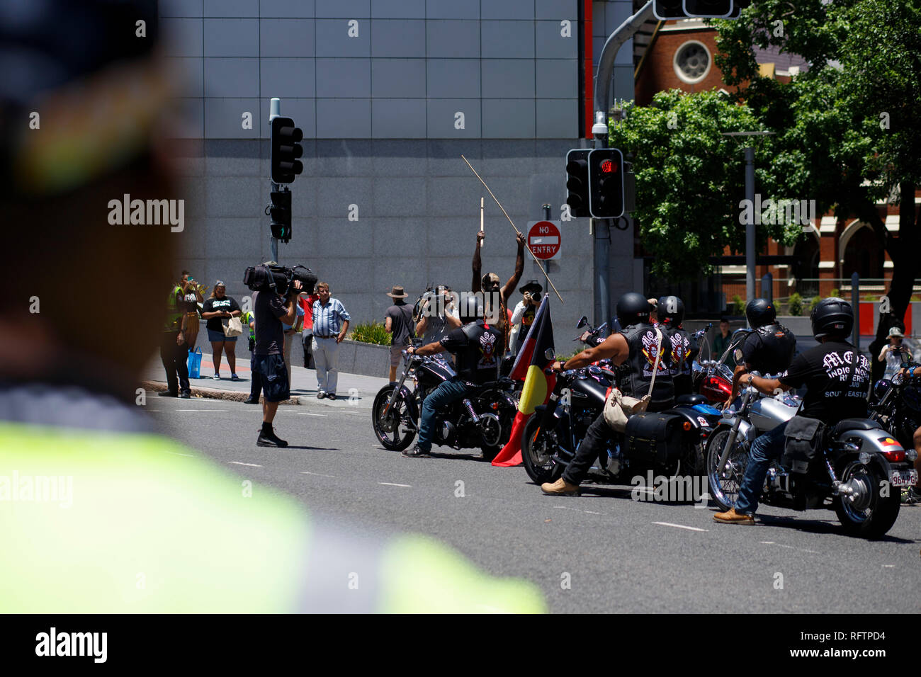 Protesters and the Indigenous Riders Club continue the march through the city at the rally on Roma Street. Indigenous protester Kamailie can be seen raising a spear among the crowd.  On the 26th of January, many Australians celebrate Australia day, but to many indigenous Australian people, it is a day synonymous with decades of systematic abuse and genocide. Several thousand protesters took the streets in Brisbane (known as Meanjin by local indigenous people) to rally for sovereignty rights and date changes. - Stock Image