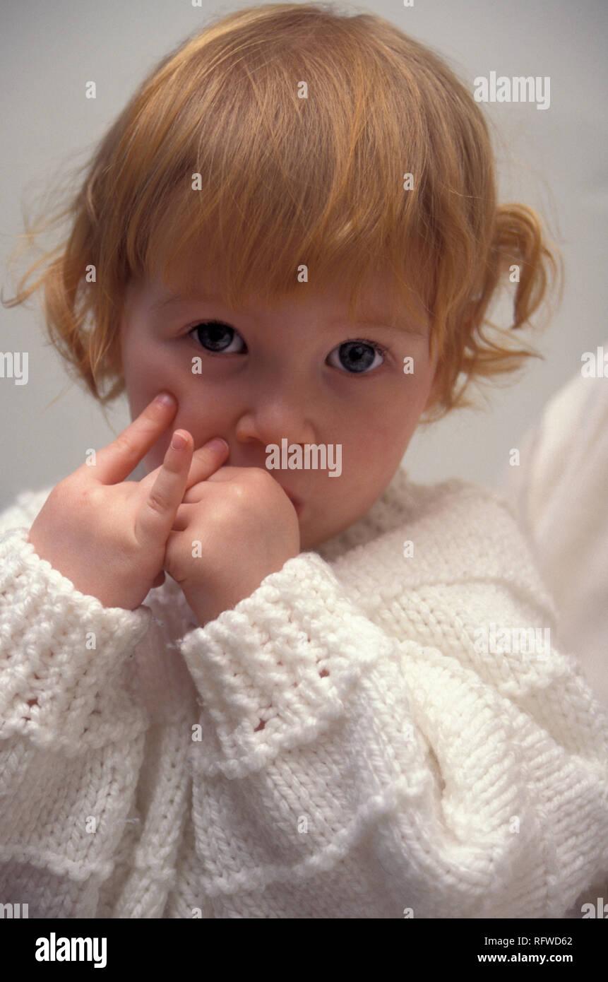 moody little girl sucking her thumb - Stock Image