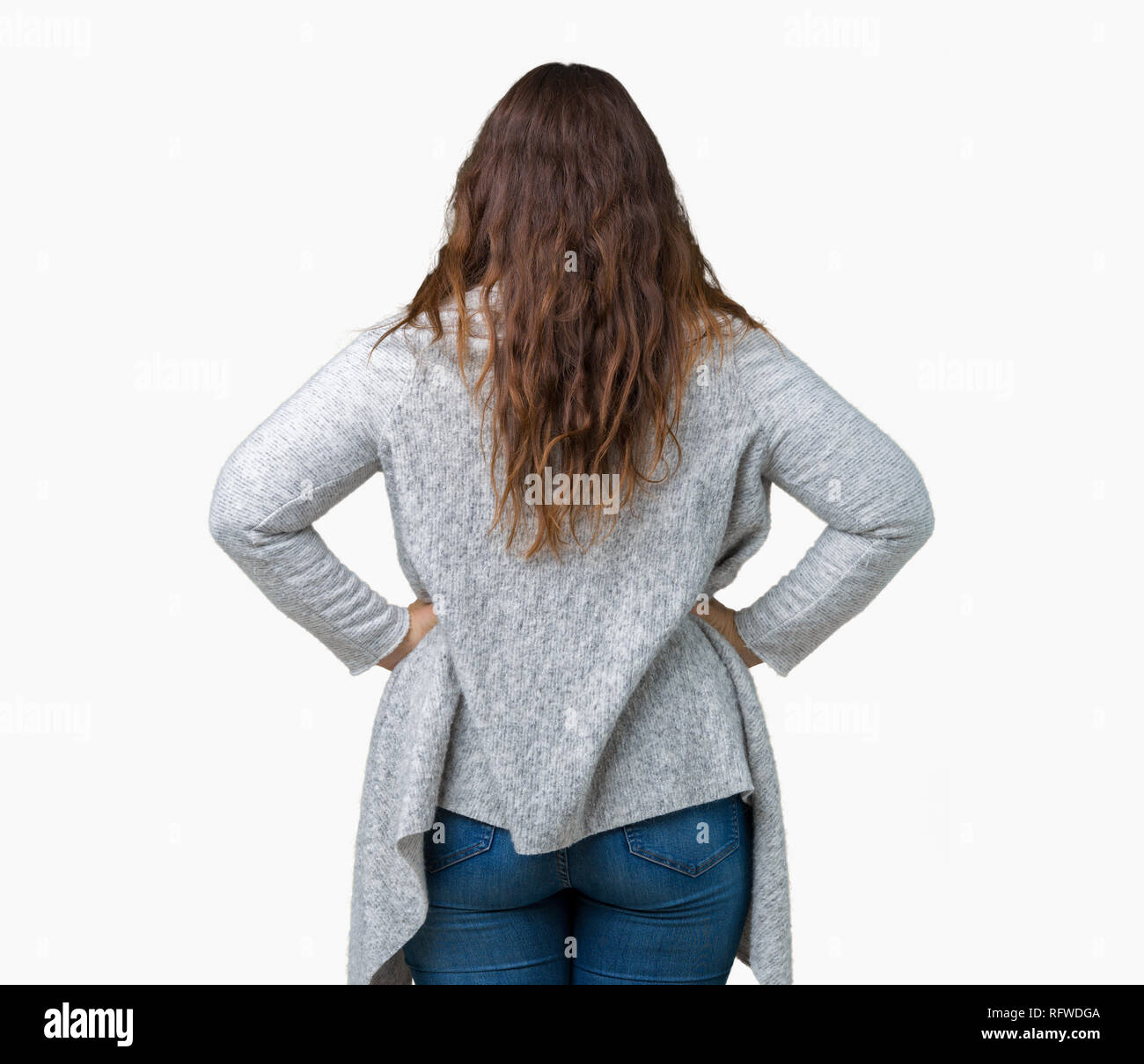 Beautiful plus size young woman wearing winter jacket over isolated background standing backwards looking away with arms on body - Stock Image