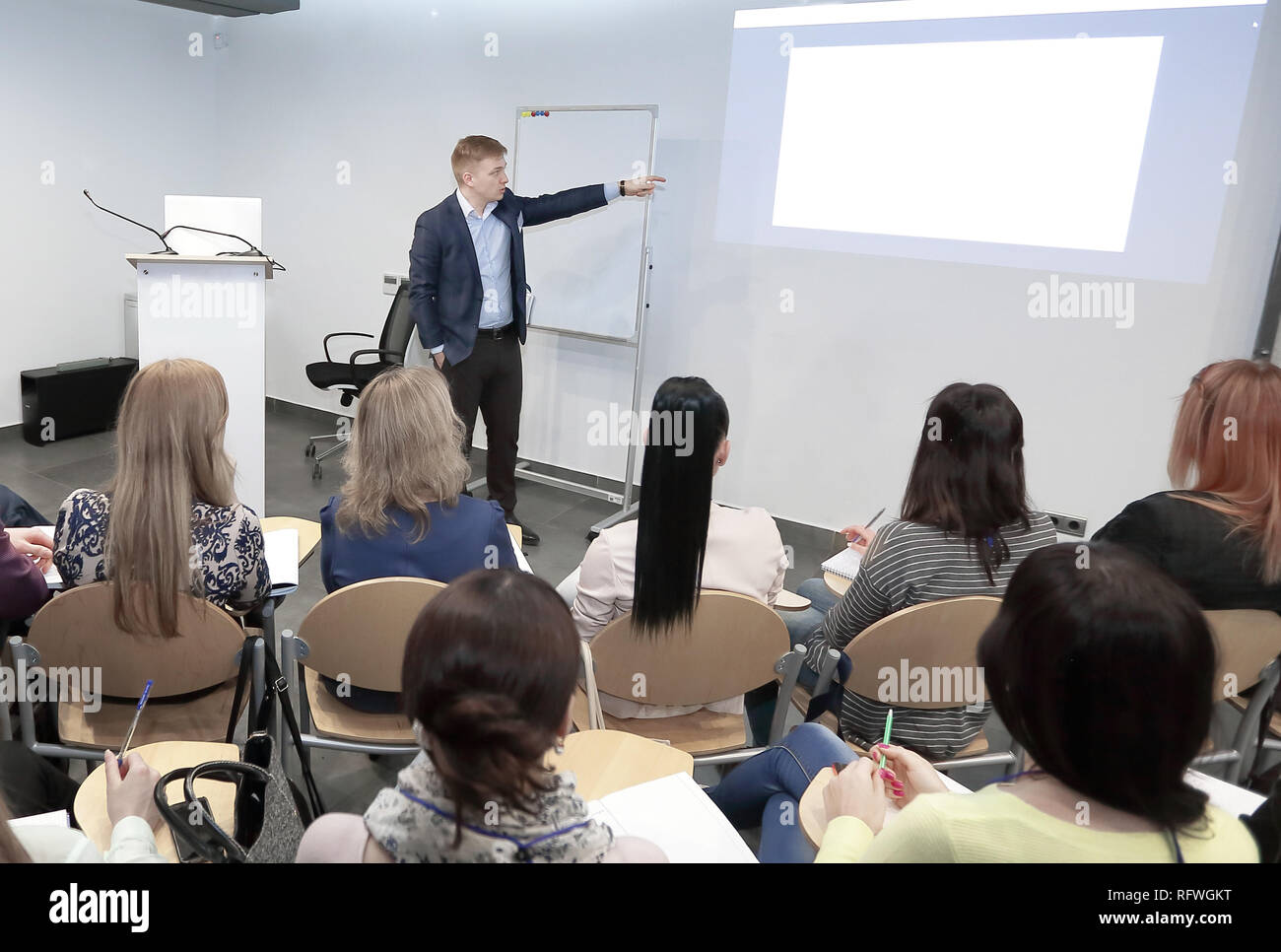 Speaker standing and lecturing on business conference in meeting hall - Stock Image
