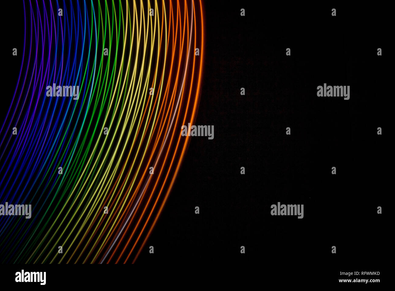 Rainbow of light. Photography made with light painting. Abstract lines with the colors of the rainbow on black background. Resource for designers. - Stock Image