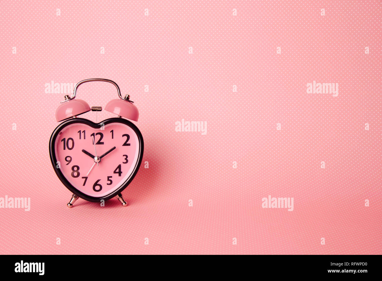 Heart shaped clock on pink background. Valentines day and love and duration concept. - Stock Image