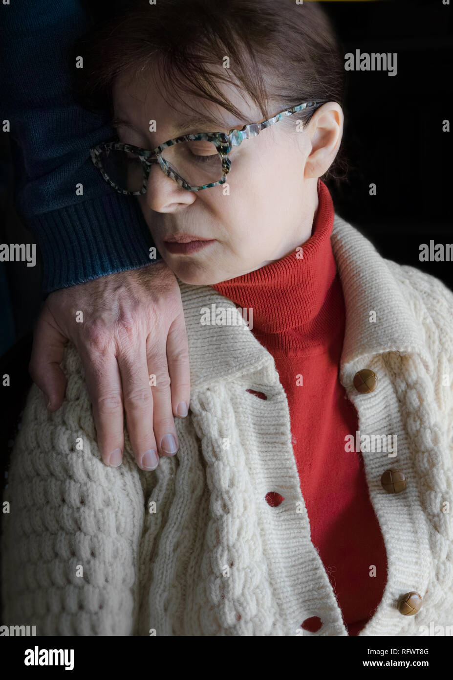 From the chiaroscuro comes the hand of a man resting on the shoulder of this woman who is sitting. She sadly turns her head towards that hand. Stock Photo