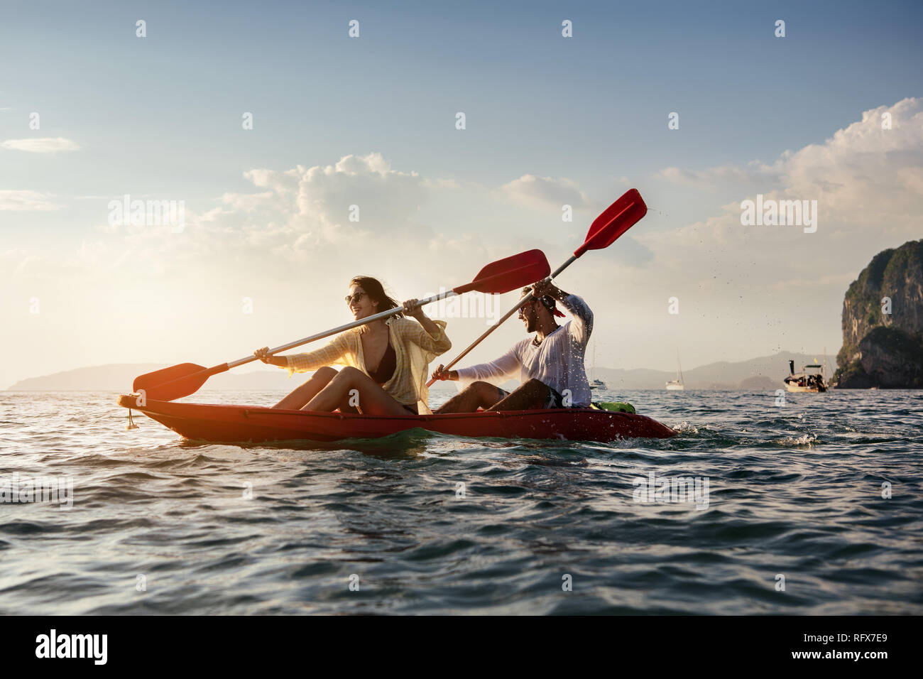 Happy couple walks by sea kayak or canoe at sunset bay. Kayaking or canoeing concept with people Stock Photo