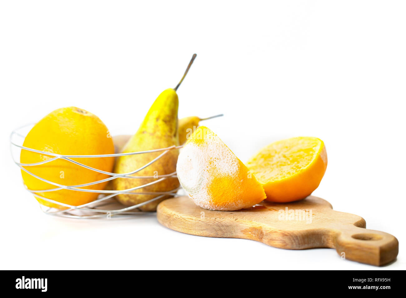 Cut in half a spoiled orange with white and green mold, against the background of other fruits - Stock Image