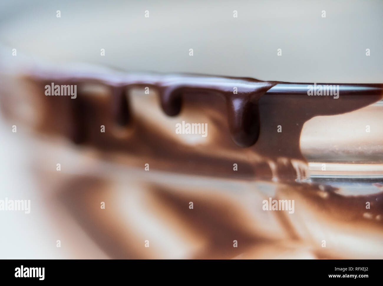 Macro closeup of liquid creamy smooth dark brown chocolate syrup icing in glass mixing bowl isolated dripping off sides edge - Stock Image