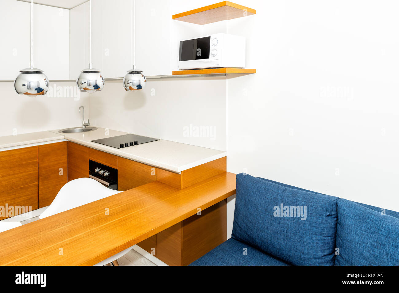 Attrayant Modern Wooden Orange Kitchen Features Cabinets In Small Apartment Studio  Bar Stool Counter Interior Design And Nobody On Blue Sofa In Minimalist Home