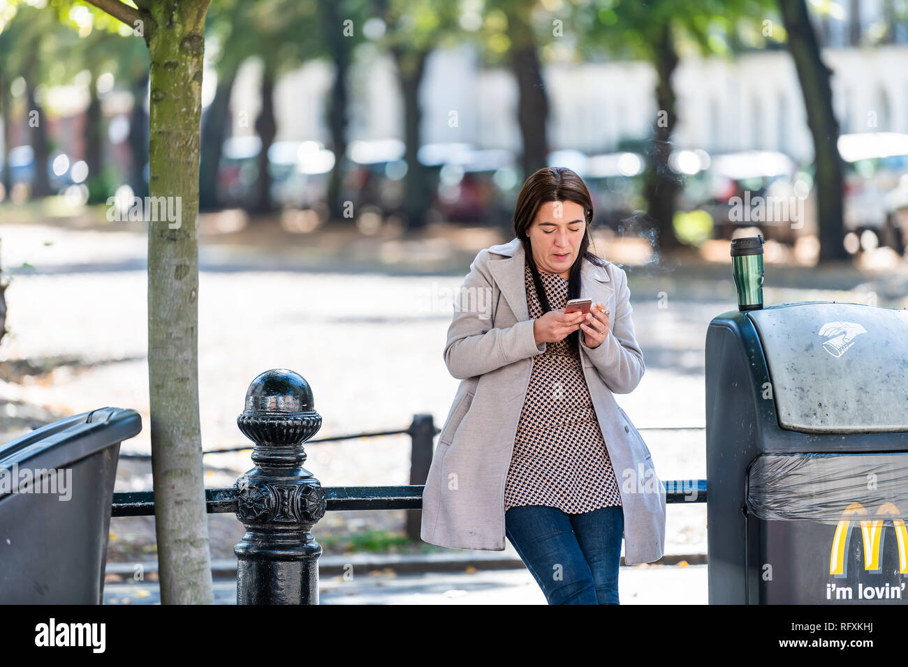London, UK - September 13, 2018: Chelsea park area with people on street pavement pedestrians and woman standing smoking break looking at phone - Stock Image