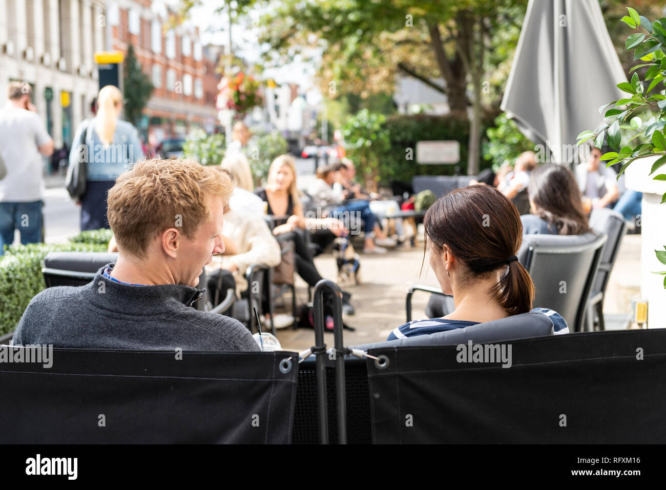 London, UK - September 16, 2018: Man and woman young couple sitting outside at cafe table in Chelsea outdoor restaurant street sidewalk at Joe and the - Stock Image