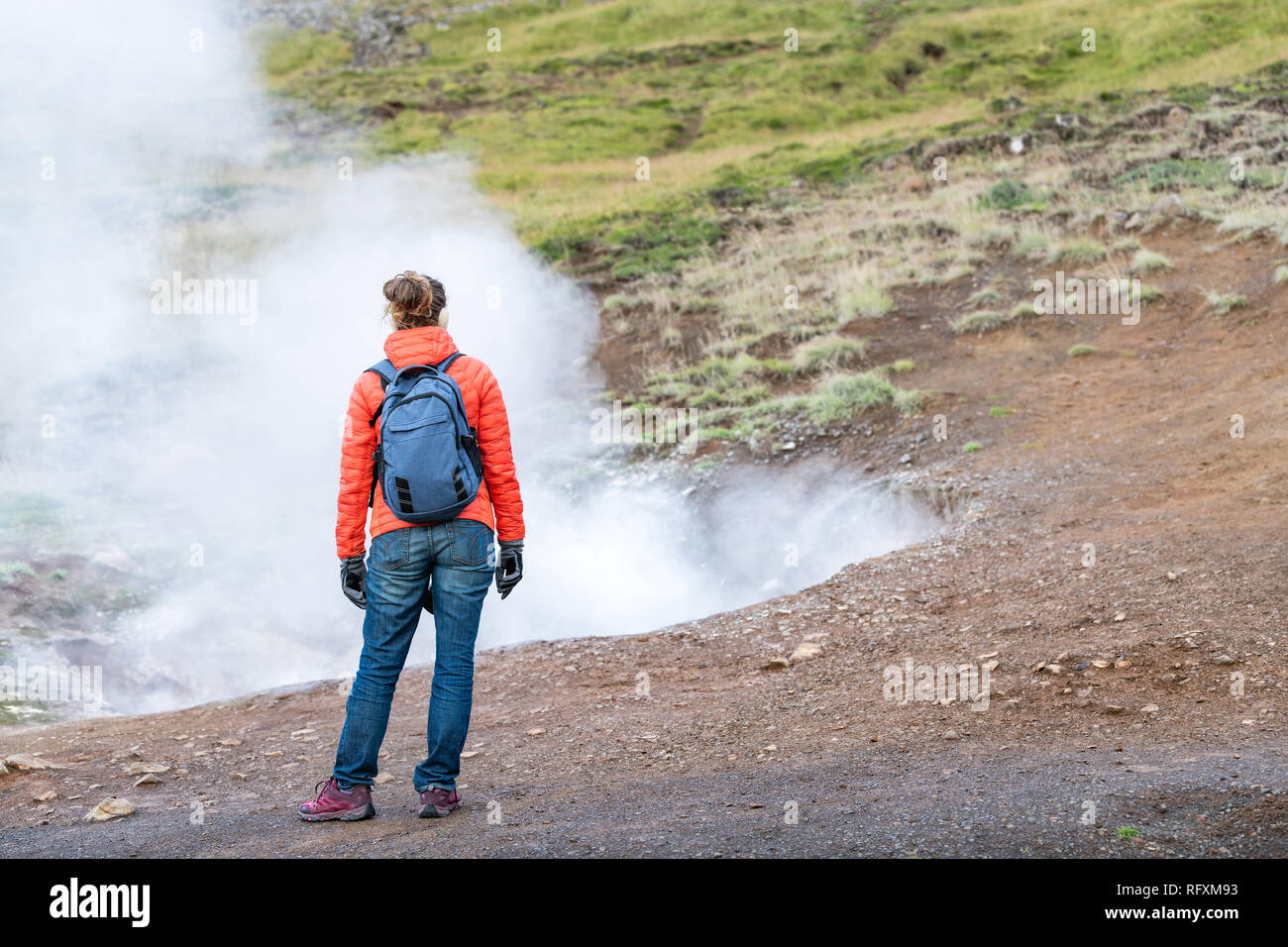 Reykjadalur, Iceland Hveragerdi Hot Springs road footpath with steam fumarole vent during autumn day in golden circle with people woman girl standing  - Stock Image