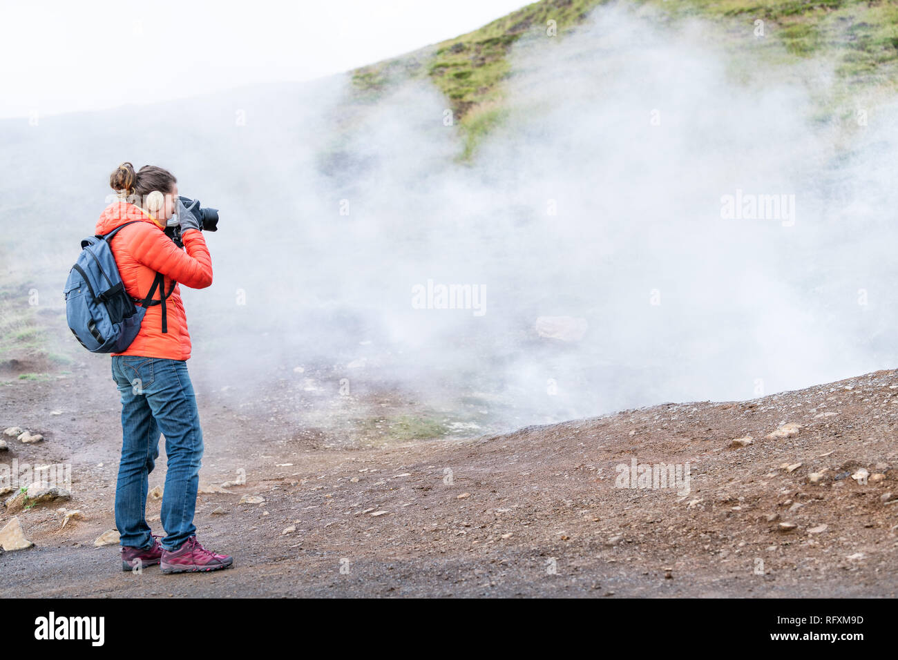 Reykjadalur, Iceland Hot Springs road footpath with steam fumarole vent during autumn day in golden circle with people woman girl taking picture photo - Stock Image