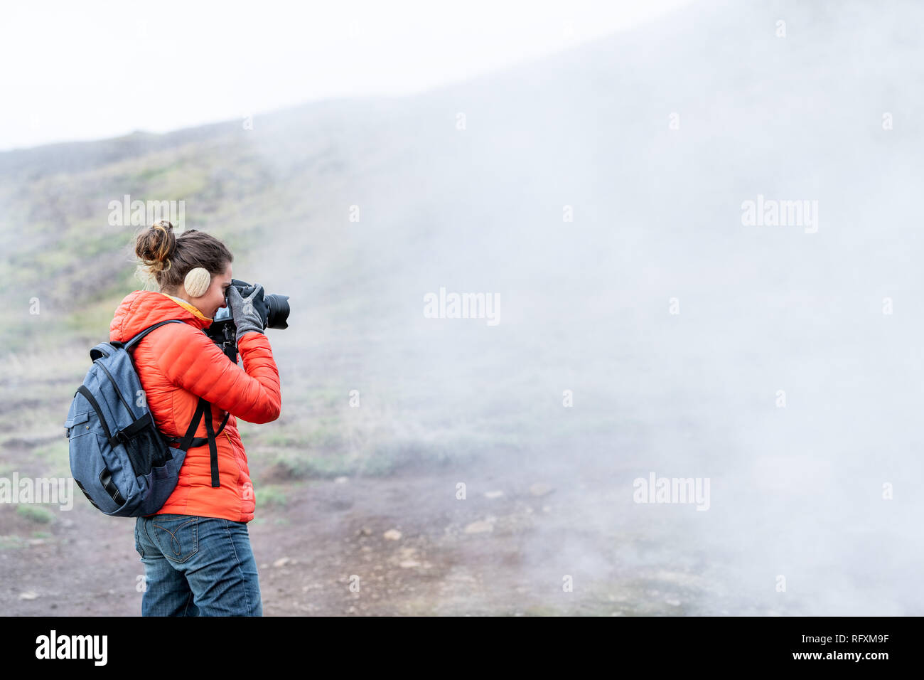Reykjadalur, Iceland Hot Springs road footpath with steam fumarole vent during cold autumn day in golden circle with people woman girl taking picture  - Stock Image