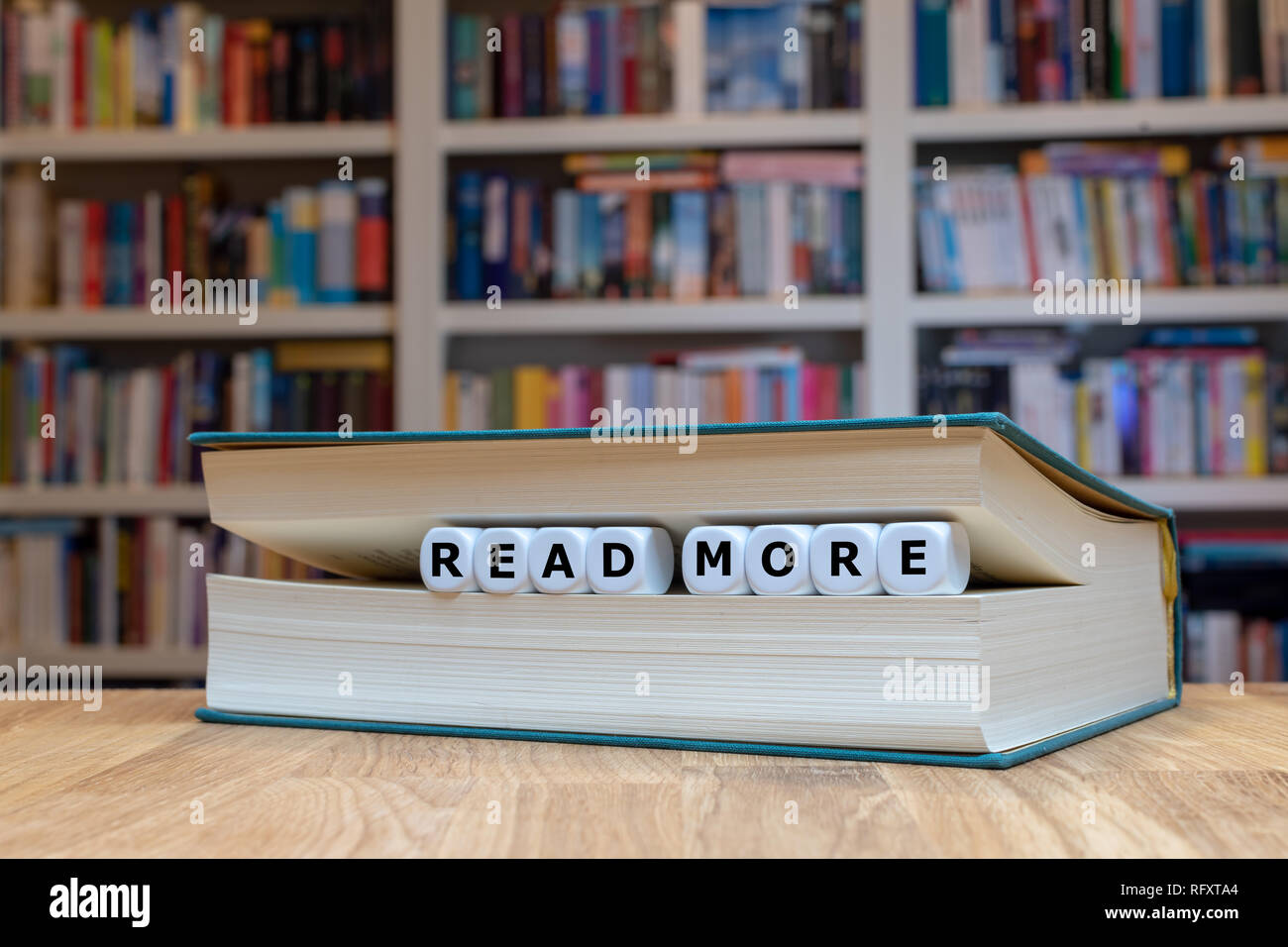 Dice in a book form the words 'read more'. Book is lying on a wooden desk infront of a bookshelf. - Stock Image