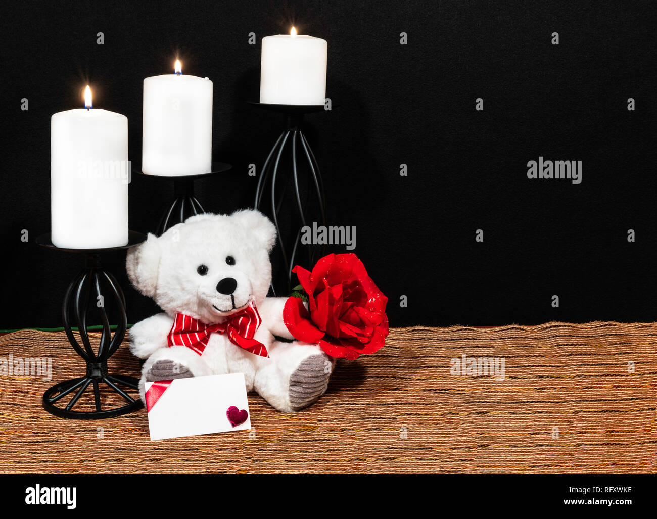 Cudlely teddy bear with red bow tie, red rose, white candles perched on black candle holders on mesh place mat and wooden table with card and dark bac - Stock Image
