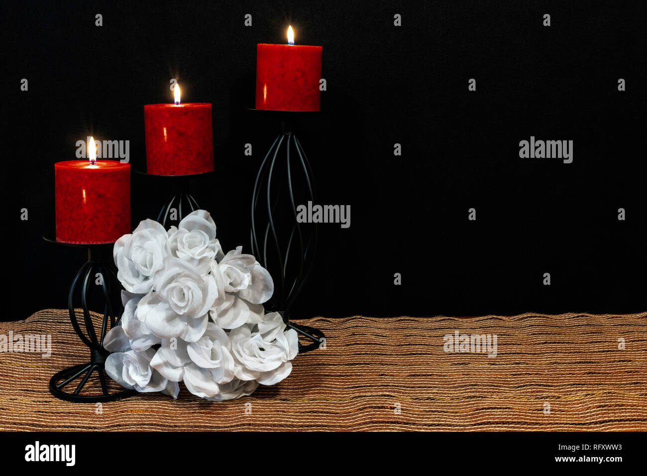 Beautiful bouquie of white roses, red candles perched on black candle holders on mesh place mat and wooden table with card and dark background. Valent Stock Photo