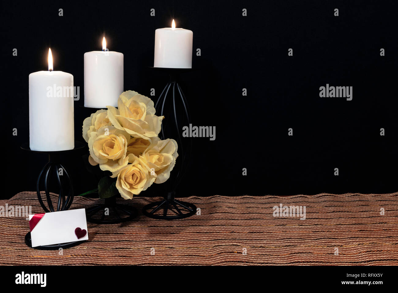 Beautiful bouquie of yellow roses, white candles perched on black candle holders on mesh place mat and wooden table with card and dark background. Val - Stock Image