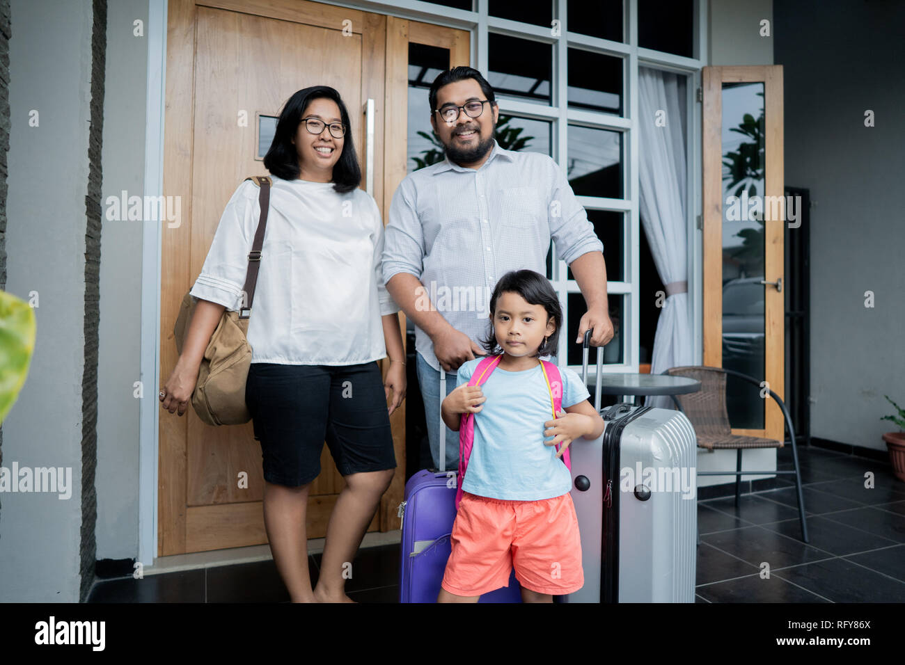 family with suitcase standing in front of their house  Stock Photo