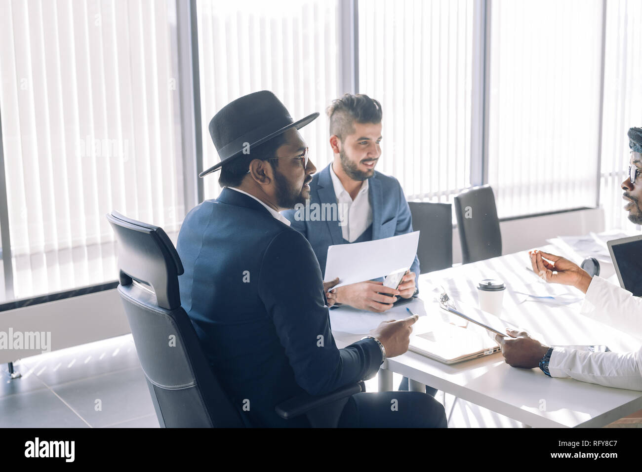 Elegant multiracial businessmen in suits gathered together for negotiating - Stock Image