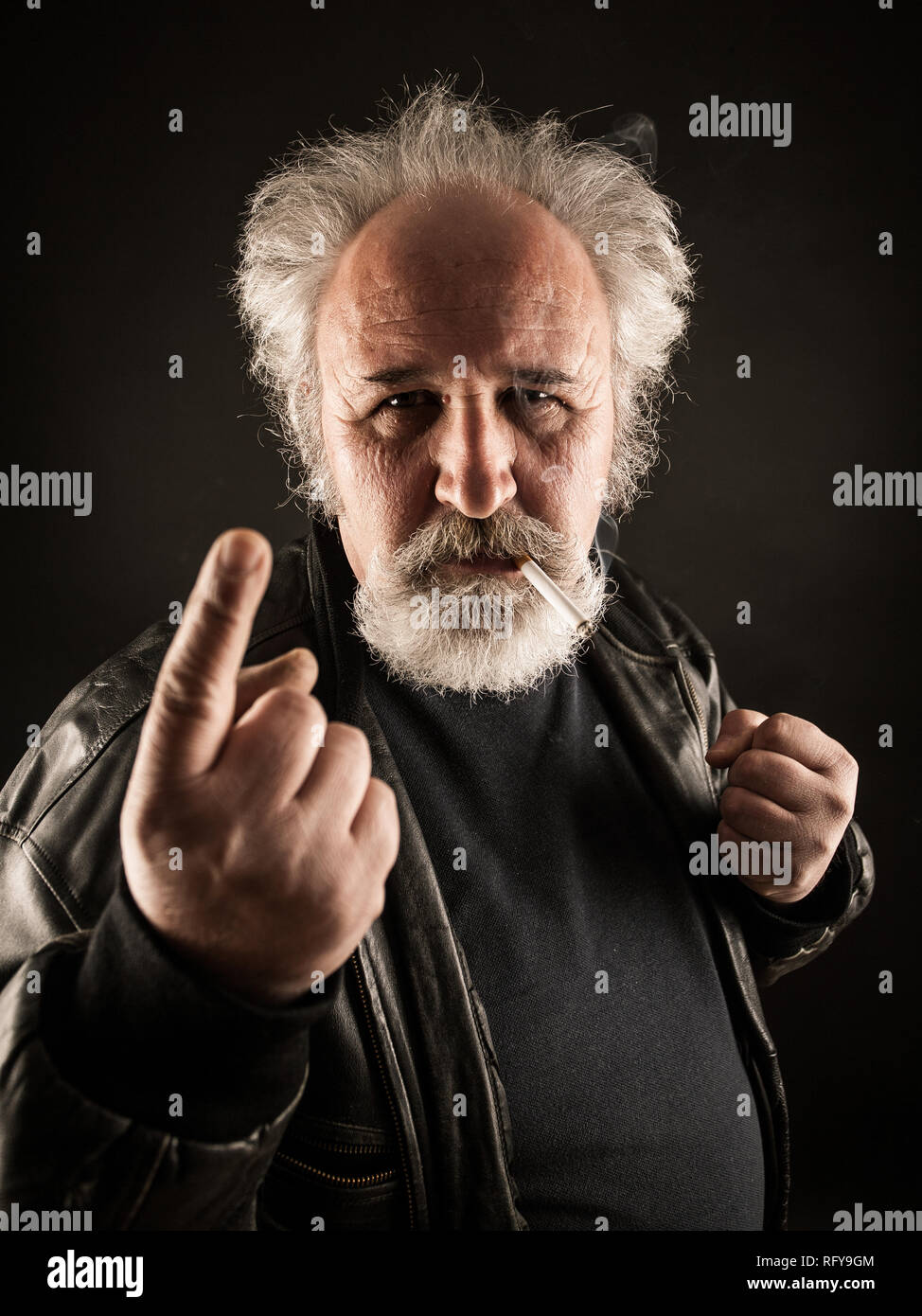 Grumpy man with cigarette against black background - Stock Image