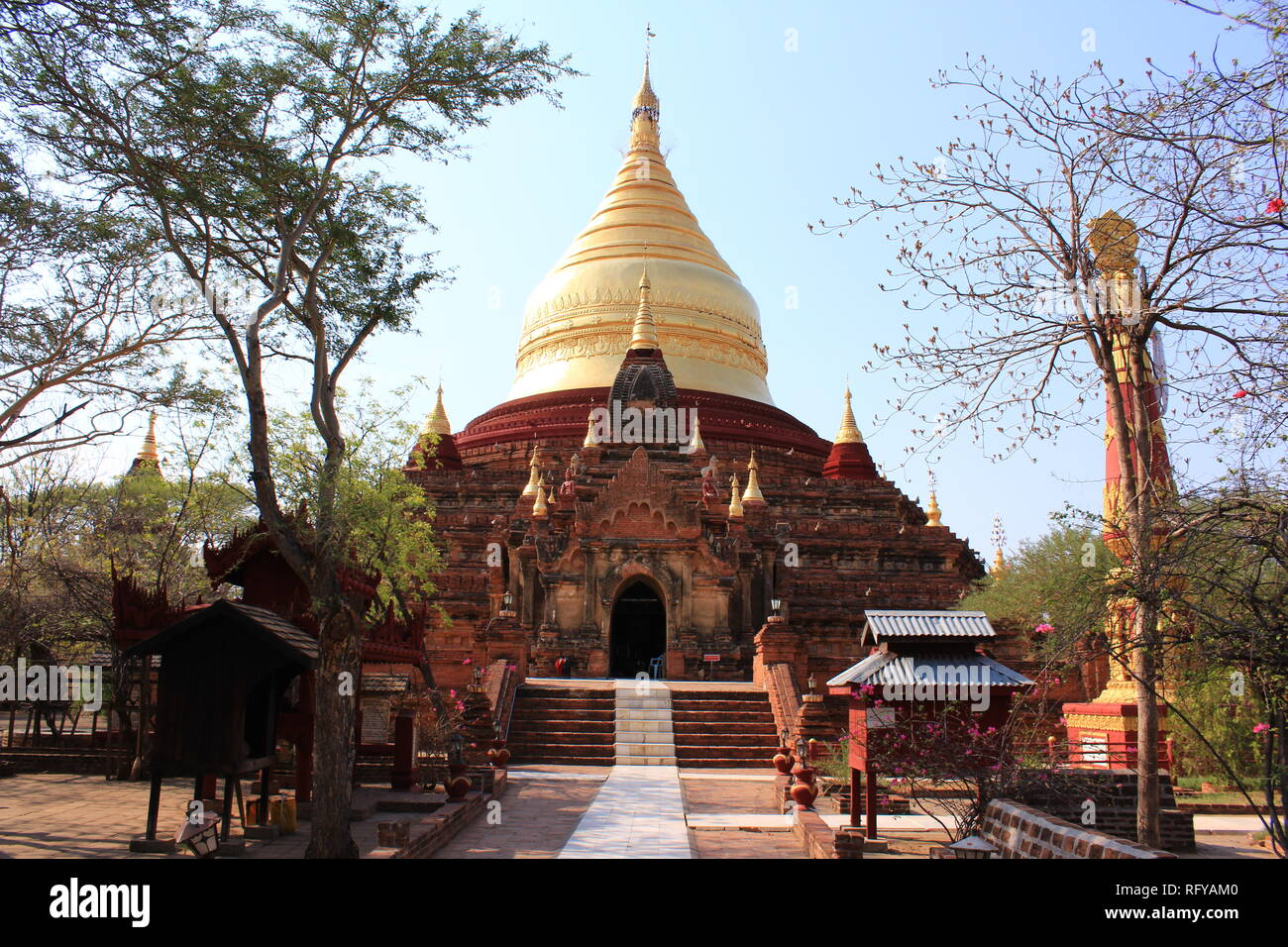 Temple with golden dome on a hot and sunny day in Bagan, Myanmar - Stock Image