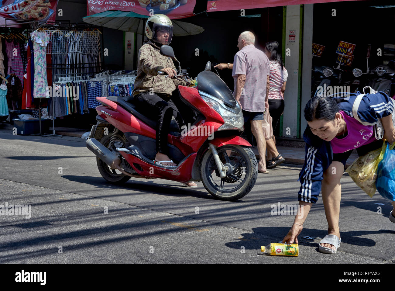 Woman taking a risk to retrieve drinks bottle with oncoming traffic. Risky action. Thailand Southeast Asia - Stock Image