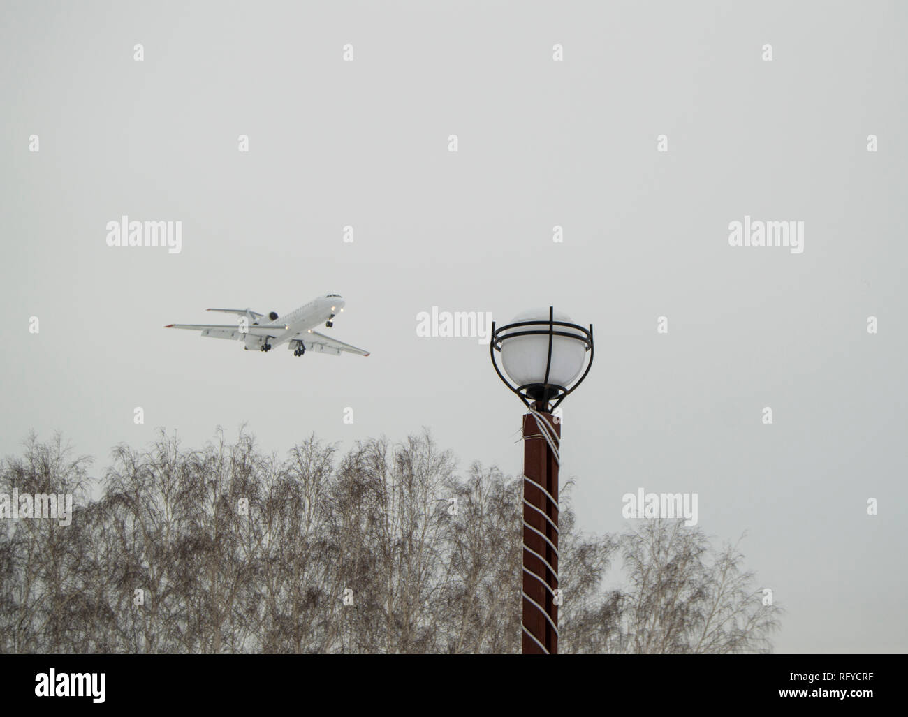 The plane flies low over the city Park and trees, cloudy winter sky. Copy space business travel adventure concept. - Stock Image
