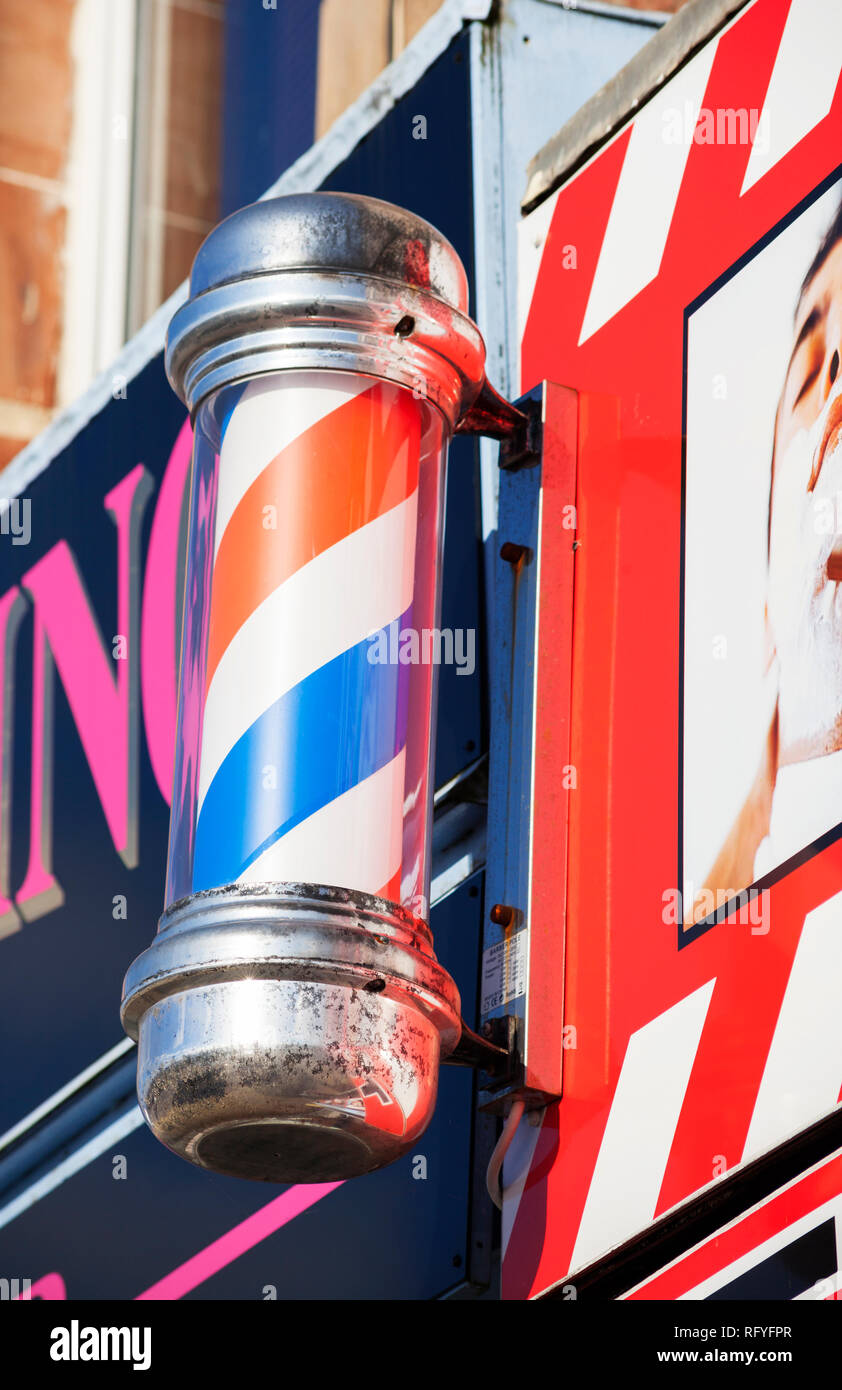 Barbers pole with red, blue and white stripes outside male hairdressers - Stock Image